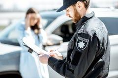 Politieagent die een boete voor een vrouwenbestuurder uitgeven stock foto's