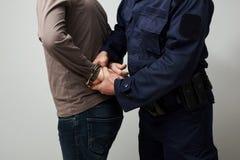 Politieagent die een illigal mens de handboeien omdoen Stock Afbeelding