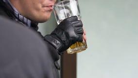 Politieagent die in fingerless handschoenen en leerjasje een glas bier drinken stock videobeelden