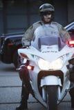 Politieagent die Helm dragen terwijl het Zitten op Motor stock foto