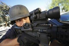 Politieagent die met Kanon in openlucht streven stock fotografie