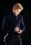 Politieagent in eenvormig schrijvend een kaartje Stock Foto's