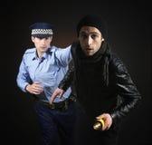 Politieagent en dief. De scène van de diefstal. stock afbeelding