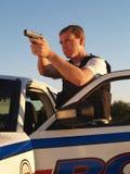 Politieagent met Getrokken Wapen Stock Foto's