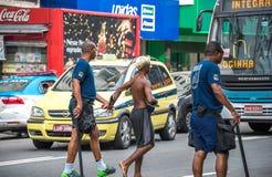 Politieagenten die arrestatie van misdadigers maken en hen leiden tot politie Stock Foto