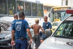 Politieagenten die arrestatie van misdadigers maken en hen leiden tot politie Stock Fotografie