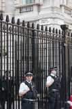 Politieagenten die de poorten neer bemannen van Stock Foto's