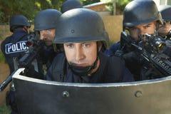 Politieagenten die Kanonnen streven terwijl Status achter Schild stock afbeeldingen