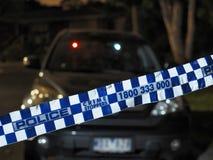 Politieband die een auto in het donker afzetten Stock Foto's