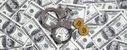 Politiehandcuffs en bitcoins leugen op een groot aantal dollarrekeningen Het concept problemen met de wet tijdens onwettige cryp royalty-vrije stock fotografie