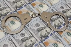 Politiehandcuffs tegen honderd dollarsrekeningen de V.S. Conceptenschending van de wet, corruptie, financiële fraude royalty-vrije stock afbeelding