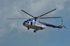 Politiehelikopter in actie met het hangen van mensen Stock Fotografie