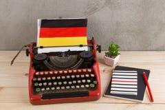 Politiek, nieuws en onderwijsconcept - rode schrijfmachine, vlag van Duitsland en notitieboekjes royalty-vrije stock afbeeldingen