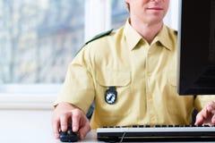 Politieman die aan bureau in afdeling werken Stock Fotografie