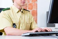 Politieman die aan bureau in afdeling werken Stock Foto
