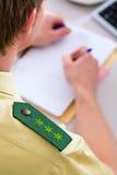 Politieman die aan bureau in post werken Stock Foto