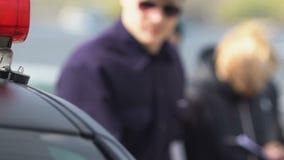 Politieman die aan mensen spreken en in auto krijgen, die conflict, ongeval oplossen stock videobeelden