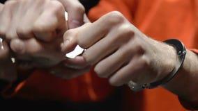 Politieman die handcuffs op misdadiger zetten, die uit ondervragingsbureau nemen stock videobeelden