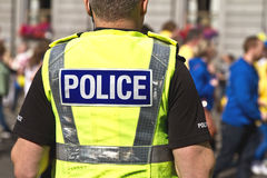 Politieman in eenvormig met woordpolitie in rug van zijn hallo-zichtjasje dat wordt geschreven Royalty-vrije Stock Foto's
