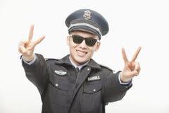 Politieman Giving Peace Sign, Studioschot Stock Afbeeldingen