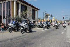 Politiemannen die op motorfietsen presteren bij Stock Fotografie