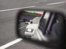 Politiewagen die door sideviewspiegel wordt bekeken Stock Afbeelding