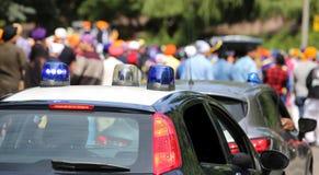 Politiewagens die sirenes opvlammen tijdens de demonstratie van mensen o Stock Foto's