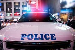 politiewagenstormlopen aan de noodoproep met lichten aangezet in de stadsstraat stock foto's