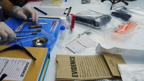 Politiewetenschapper die in Criminalistisch Laboratorium, kogelshell analyse werken stock footage