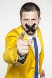 Politik mit Band auf seinem Mund, der auf Sie zeigt lizenzfreie stockfotos