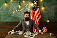 Politiker: sitt med bunten av USA-valuta royaltyfria foton
