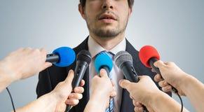 Politikern talar ang som ger intervju till reporter Många mikrofoner som antecknar honom Arkivbild