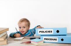 Politiques et procédure - jeune garçon avec la pile de grippage de deux bureaux Photographie stock libre de droits