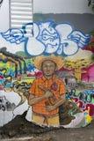 Politische Graffiti des jungen Mannes umgeben durch Klimadisa Stockfotografie