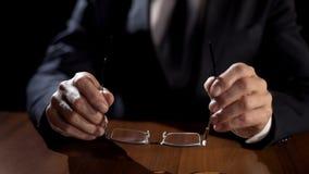 Politischer Beamter, der Brillen beim Denken über wichtiger Entscheidung hält lizenzfreie stockbilder
