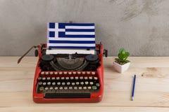 Politisk, nyheterna- och utbildningsbegrepp - röd tappningskrivmaskin, flagga av Grekland, blyertspenna royaltyfri foto