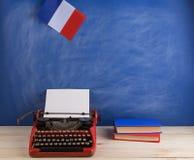 Polityczny, wiadomość i edukacja pojęcie, - czerwona maszyna do pisania, flaga Francja, rezerwuje na stole zdjęcia stock