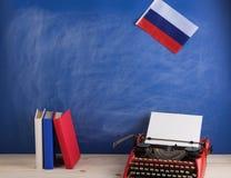 Polityczny, wiadomość i edukacja pojęcie, - czerwona maszyna do pisania, flaga Rosja, rezerwuje na stole fotografia royalty free