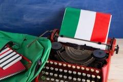Polityczny, wiadomość i edukacja pojęcie, flaga Włochy, zielony plecak i materiały na stole - czerwona maszyna do pisania, zdjęcia royalty free