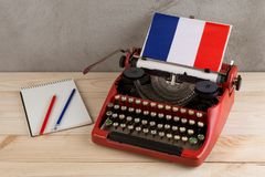 Polityczny, wiadomość i edukacja pojęcie, - maszyna do pisania, flaga Francja, notatnik na szarość cementuje tło obrazy stock