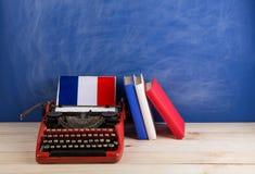 Polityczny, wiadomość i edukacja pojęcie, - czerwona maszyna do pisania, flaga Francja, rezerwuje na stole zdjęcie royalty free