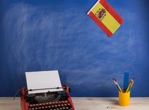 Polityczny, wiadomo?? i edukacja poj?cie, - czerwona maszyna do pisania, flaga Hiszpania, materia?y na stole obraz stock