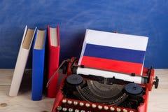 Polityczny, wiadomość i edukacja pojęcie, - czerwona maszyna do pisania, flaga Rosja, rezerwuje na stole zdjęcie royalty free