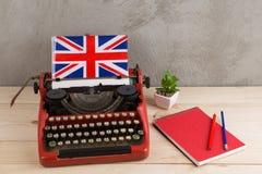 Polityczny, wiadomość i edukacja pojęcie, - czerwona maszyna do pisania, flaga Zjednoczone Królestwo, rezerwuje na stole fotografia stock