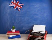 Polityczny, wiadomość i edukacja pojęcie, - czerwona maszyna do pisania, flaga Zjednoczone Królestwo, rezerwuje na stole obrazy stock