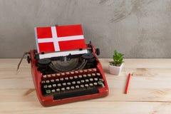 Polityczny, wiadomość i edukacja pojęcie, - czerwona rocznik maszyna do pisania, flaga Dani, ołówek fotografia royalty free