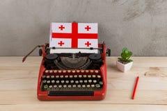 Polityczny, wiadomość i edukacja pojęcie, - czerwona rocznik maszyna do pisania, flaga Gruzja, ołówek zdjęcia royalty free