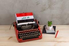 Polityczny, wiadomość i edukacja pojęcie, - czerwona rocznik maszyna do pisania, flaga Irak, ołówek obraz royalty free