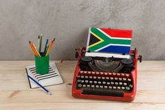 Polityczny, wiadomość i edukacja pojęcie, - czerwona rocznik maszyna do pisania, flaga Południowa Afryka, ołówek zdjęcie royalty free