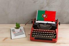 Polityczny, wiadomość i edukacja pojęcie, - czerwona rocznik maszyna do pisania, flaga Portugalia, ołówek, notepads zdjęcie royalty free